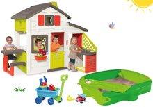 Komplet hišica Prijateljev Smoby s kuhinjo in zvončkom, peskovnik Sandy s pokrivalom in voziček za vlečenje